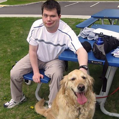 Service dog sitting at a picnic table at the park with his owner